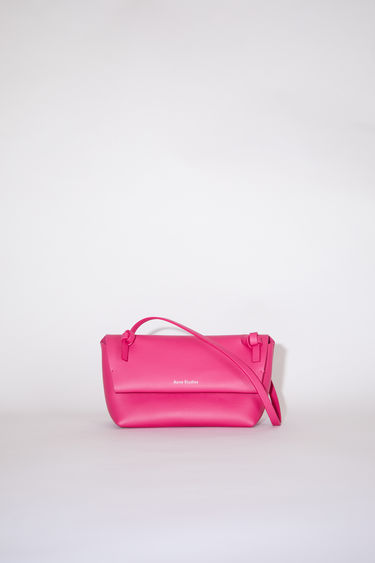 Acne Studios fuchsia pink flap purse features twisted knots inspired by traditional Japanese obi sashes.