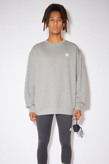 Acne Studios light grey melange sweatshirt is crafted from midweight loopback jersey to an oversized silhouette with dropped shoulders and accented with a tonal face-embroidered patch on the chest.