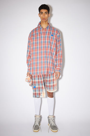 Acne Studios pink/blue relaxed button down shirt is made of organic cotton flannel with a face patch at the chest.