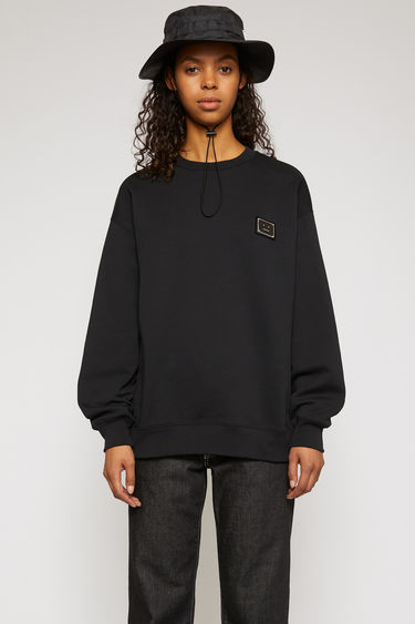 Acne Studios black sweatshirt is crafted from midweight loopback jersey to an oversized silhouette and features a polished metal logo plaque that depicts a face motif in black.