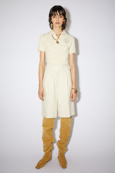 Acne Studios cream beige belted shorts are made of cotton with a relaxed fit.
