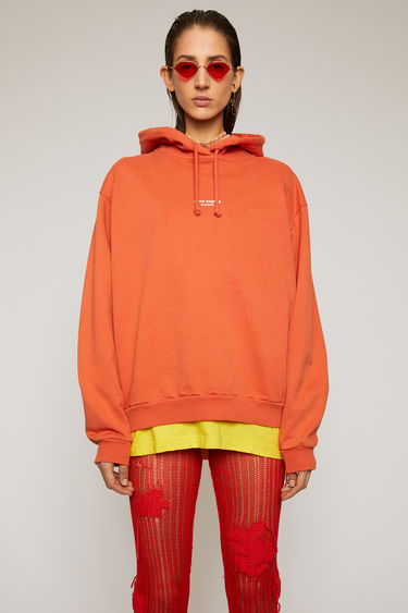 Acne Studios poppy red hooded sweatshirt is made from cotton jersey that's been garment dyed for a soft, washed-out finish. It's shaped for an oversized fit and features a reversed logo purposely printed imprecisely across the front.