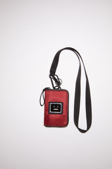 Acne Studios burgundy pouch wallet is made from technical ripstop with a detachable lanyard. It has a zipper closure with a pull and is accented with a polished metal logo plaque with a face motif in black.