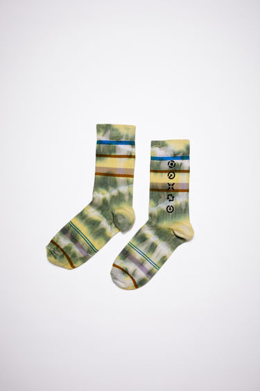 Acne Studios khaki green socks is made from tie-dyed repurposed cotton blend featuring a symbol print on the side.