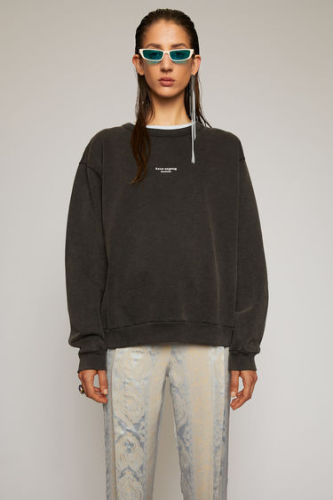 Acne Studios black sweatshirt is made from cotton jersey that has been garment dyed for a soft, washed-out finish and it features a reversed logo printed across the chest.