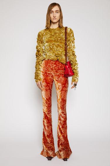 Acne Studios rust orange trousers are crafted from soft velvet and woven with a floral motifs. They're cut to sit high on the waist and flare from below the knees.