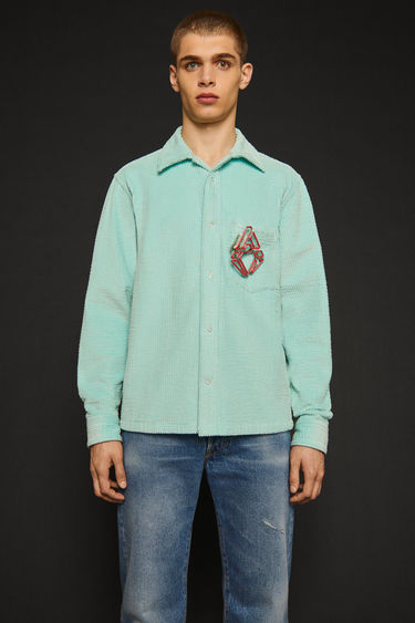 Acne Studios mint blue shirt is made from wide-ribbed corduroy with a straight hem and has a chest patch pocket and snap buttons through the placket and cuffs.