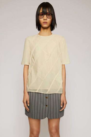 Acne Studios beige blouse is diagonally assembled with multi-tonal panels of crepe du chine and constructed with inverted French seams with raw edges.
