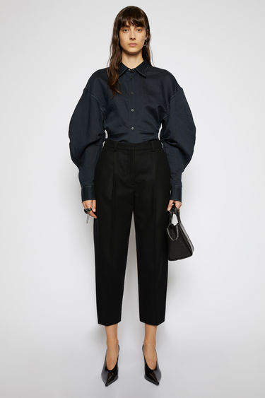 Acne Studios black trousers cut with a high waist and cropped, tapered legs, and are pleated along the front for subtle volume.