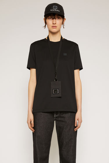 Acne Studios black t-shirt is cut from a lightweight cotton jersey to a slim-fitting silhouette with a round neckline and accented with a tonal face-embroidered patch on the chest.