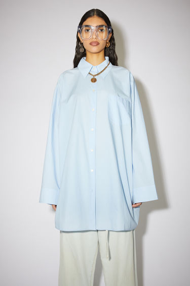 Acne Studios sky blue is crafted from lightweight blended cotton to an oversized, boxy profile that drapes loosely above the knee. It features a point collar, chest patch pocket and a button-down front placket.