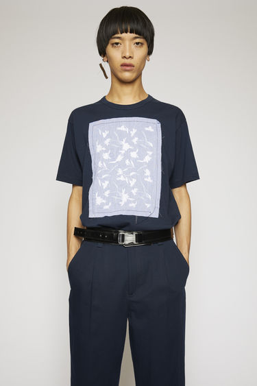 Acne Studios navy blue t-shirt is crafted from lightweight cotton jersey and features intricate floral embroidery on the patch. It's purposefully finished with loose hanging threads for a subtle note of texture.