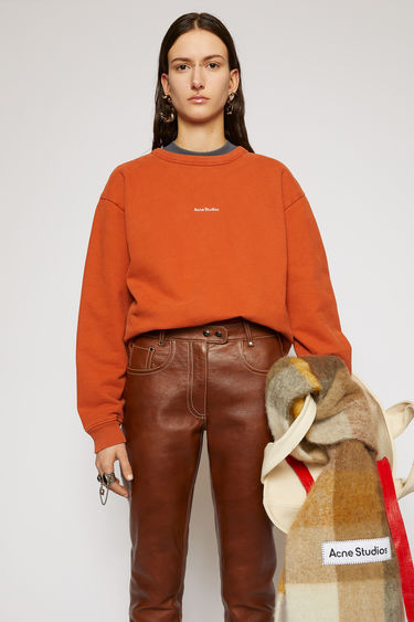 Acne Studios pumpkin orange sweatshirt is made from pigment-dyed jersey that's lightly faded along the seams. It's cut to a relaxed silhouette with dropped shoulders and features a raised logo print on front.