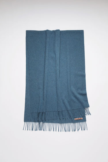 Acne Studios dusty blue oversized fringed scarf is made of pure wool, featuring a label in one corner.