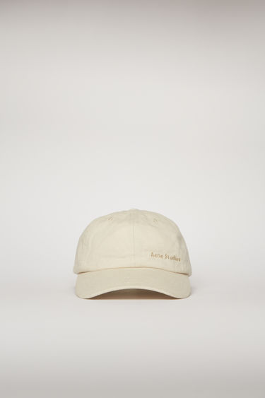 Acne Studios ecru beige cap is crafted from cotton twill to a six-panel construction with a curved brim and finished with an embroidered logo on the front.