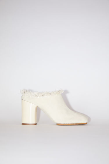 Acne Studios ecru beige fringed canvas mules have square toes and chunky heels.