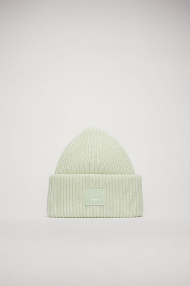Acne Studios pastel green beanie is rib-knitted from soft wool and accented with a face-embroidered patch on the front.