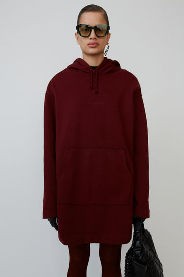 Acne Studios chocolate brown hoodie dress is shaped to an oversized fit and accented with a debossed logo on the front.