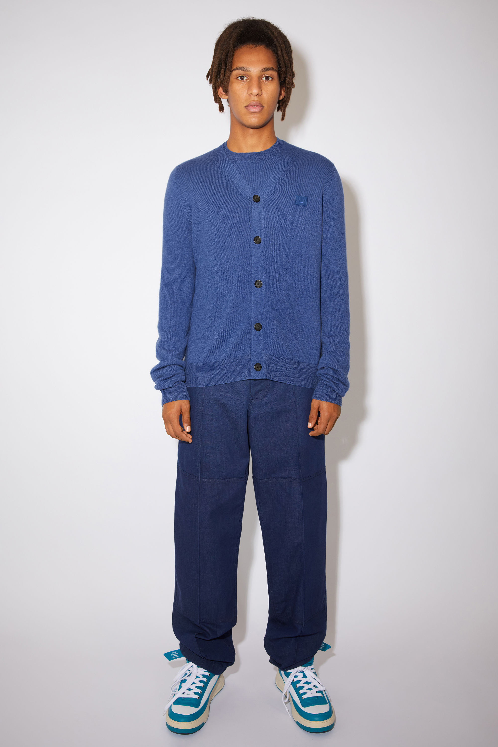 Acne Studios dusty blue v-neck cardigan sweater is made from wool with a face logo patch and ribbed details. 001