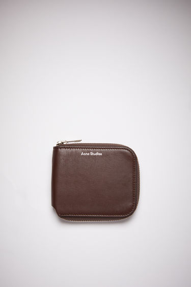 Acne Studios dark brown compact zip wallet is made of smooth leather with two card slots, a bill sleeve, and a zipper closure.