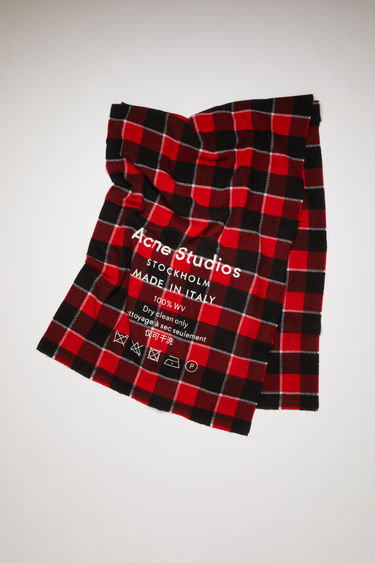 Acne Studios red/black scarf is patterned with a check design and features a screen printed Acne Studios logo and care label.