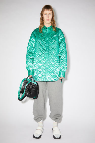 Acne Studios jade green shiny, lightweight jacket features face quilting and a tonal face patch at the chest.