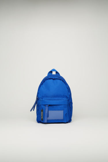 Acne Studios deep blue mini backpack is crafted to a structured silhouette with a front zip pocket and features an adjustable crossbody strap and a transparent card pocket.