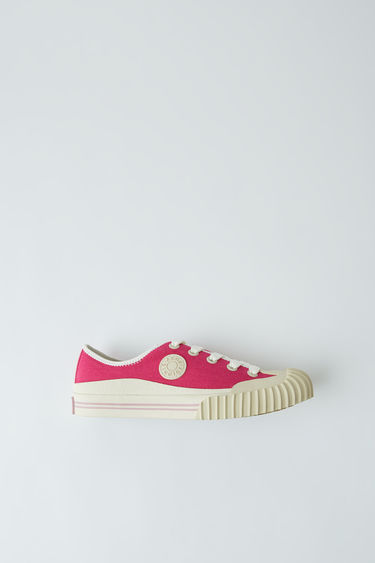 Acne Studios fuchsia pink low top, lace up sneakers featuring Acne Studios logo patch.