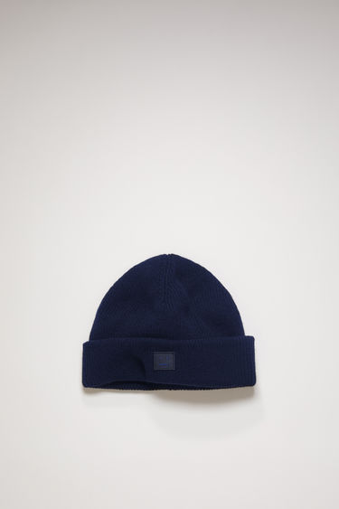 Acne Studios navy blue beanie is knitted with wool and lycra for a closer fit and accented with a tonal face-embroidered patch on front.
