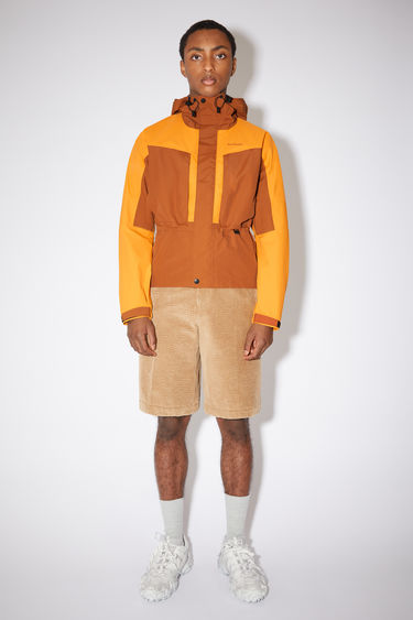 Acne Studios cognac Brown/Saffron Orange colour block hooded jacket is made is made of a three layer nylon fabric with a technical membrane at the inside the jacket has water proof seams and Acne Studios branding at the chest.