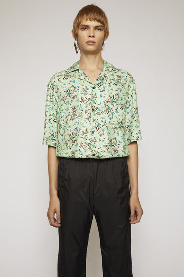 Acne Studios pastel green shirt is cut from a lightweight viscose to a boxy silhouette and patterned with the seasonal flower print.