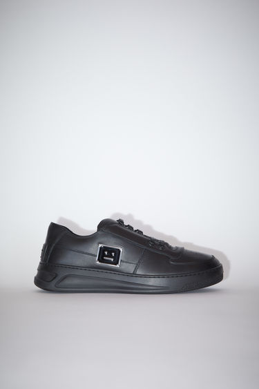 Acne Studios black/black lace-up sneakers are made of calf leather with a round toe and a face motif on the back sole.