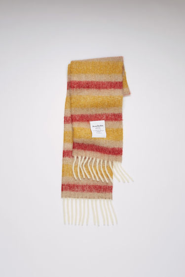 Acne Studios beige/red/yellow striped scarf is spun from a blend of alpaca, wool and mohair yarns in a relaxed long-length silhouette that drapes through the body. It's finished with a soft, brushed texture and a logo patch above the fringed edges.