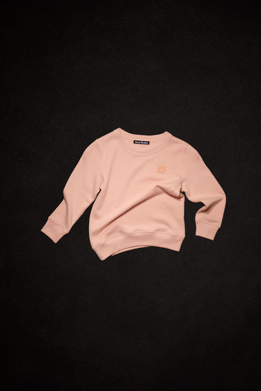 Acne Studios powder pink crew neck sweatshirt is made of organic cotton with a face patch and ribbed details.