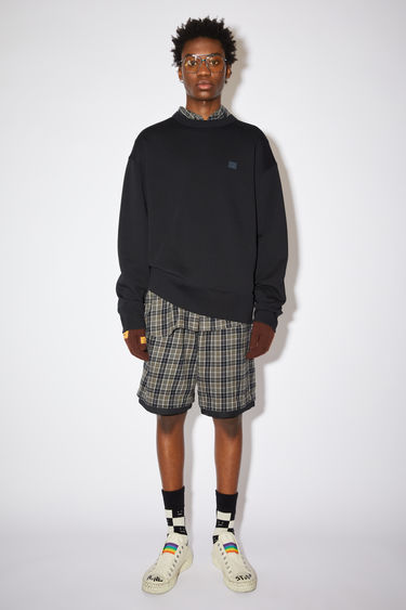 Acne Studios black oversized crew neck sweatshirt is made of organic cotton with a face patch and ribbed details.