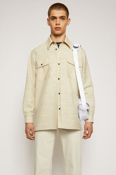 Acne Studios off white melange overshirt is crafted to an oversized silhouette with dropped shoulders and features two chest flap pockets, two side welt pockets and a point collar.