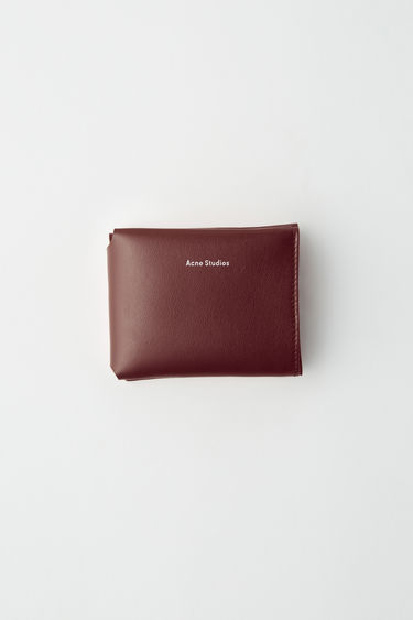 Acne Studios burgundy card holder, folded in half with four interior flap pockets for cards.