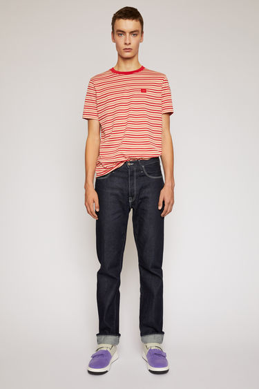 Acne Studios indigo blue jeans are cut to a straight fit and accented with contrasting white topstitching and a face-embroidered patch.