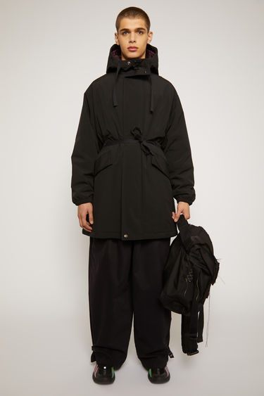 Acne Studios black fishtail parka crafted to a relaxed silhouette with checked flannel and quilted lining and has a drawstring hood, waist and hem to adjust the fit.