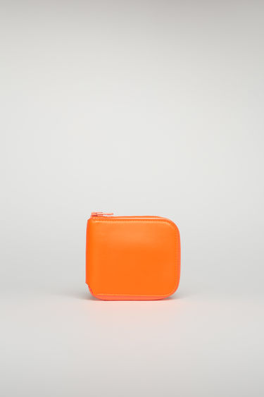 Acne Studios fluo orange zip wallet is crafted from smooth leather and stamped with a white branding across the front. Secured with a zip fastening, it's equipped with two card slots and a note compartment.