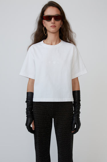 Acne Studios optic white t-shirt is cut to a boxy shape with a cropped length and features an embossed logo on the chest.