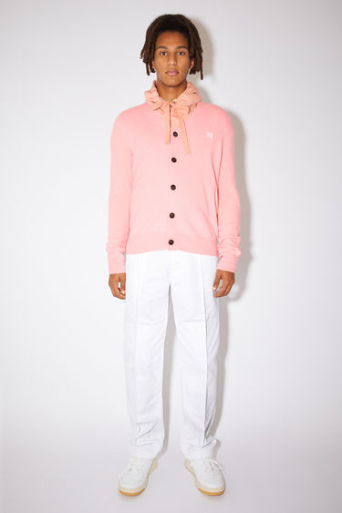 Acne Studios blush pink v-neck cardigan sweater is made from wool with a face logo patch and ribbed details.