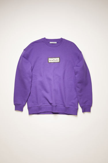 Acne Studios electric purple sweatshirt is crafted for an oversized fit from midweight loopback jersey and adorned with a label patch on front.
