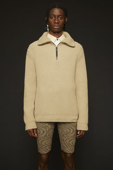 Acne Studios cold beige sweater is rib-knitted from a cotton blend with a funnel neck and then completed with a half-zip closure through the front.