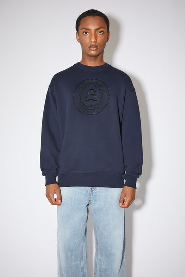 Acne Studios navy oversized sweatshirt is made of cotton with an embroidered logo design on the front.