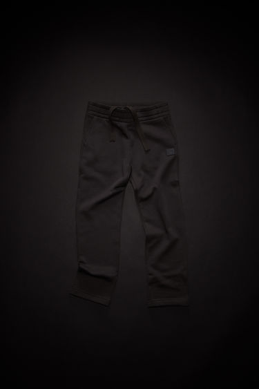 Acne Studios children's black drawstring sweatpants are made of organic cotton with an elastic waist and a face logo patch.