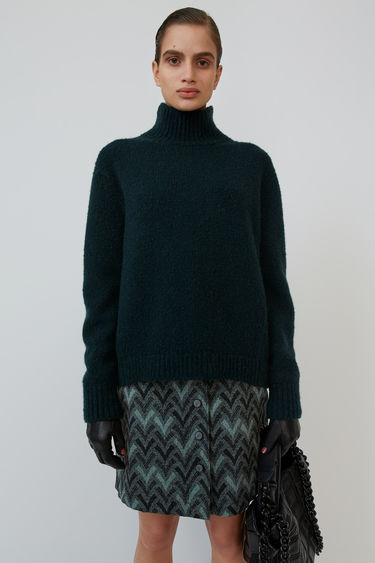 Acne Studios bottle green is a high neck sweater shaped with slanted side seams to create a cocoon-like silhouette.