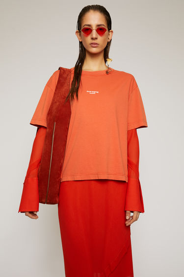 Acne Studios poppy red t-shirt is made from cotton jersey that has been garment dyed for a soft, washed-out finish and features a reversed logo printed across the chest.