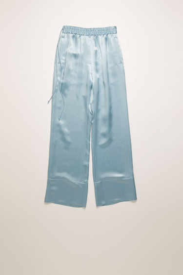 Acne Studios powder blue satin trousers are cut to a relaxed fit with straight legs and feature an elasticated waist with drawstrings at side.