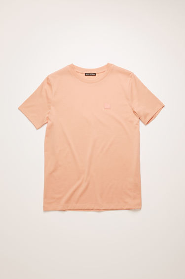 Acne Studios pale pink crew neck t-shirt is made of organic cotton with a face logo patch and ribbed neckline.